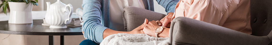 Caregiver holding patient's hands