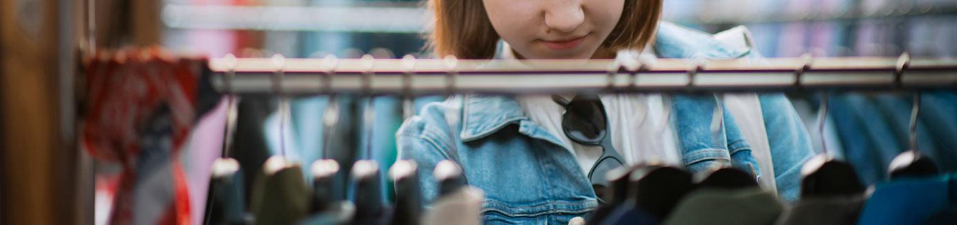 Girl looking at clothing at thrift store