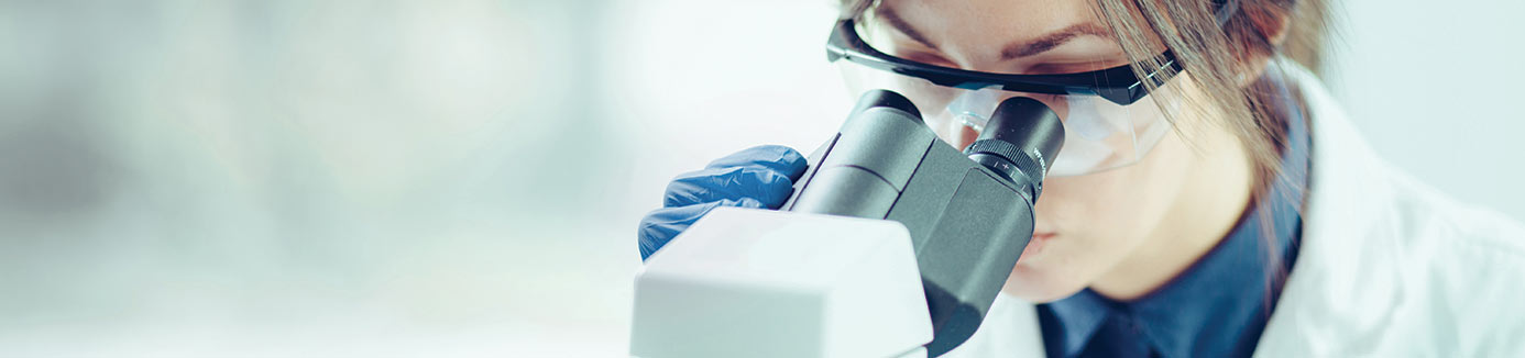Physician reviewing lab results through microscope