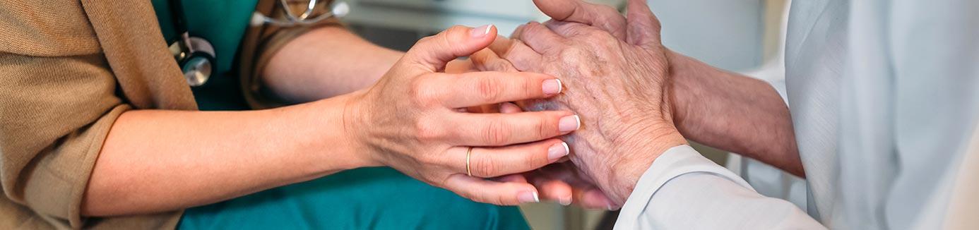 Doctor holding hands of elderly patient