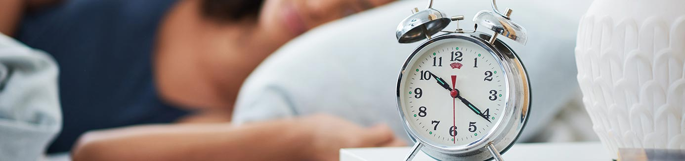 Alarm clock with someone sleeping in background