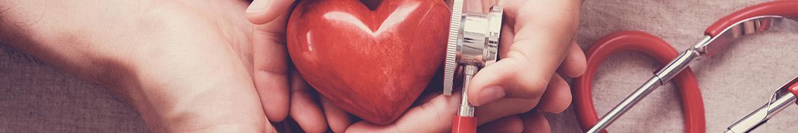 Hands holding a wooden heart