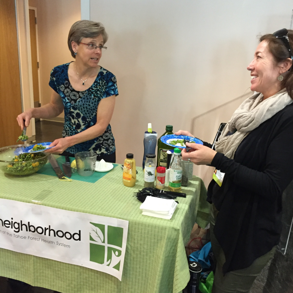 Betsy Taylor, RD demonstrates healthy recipe for community member