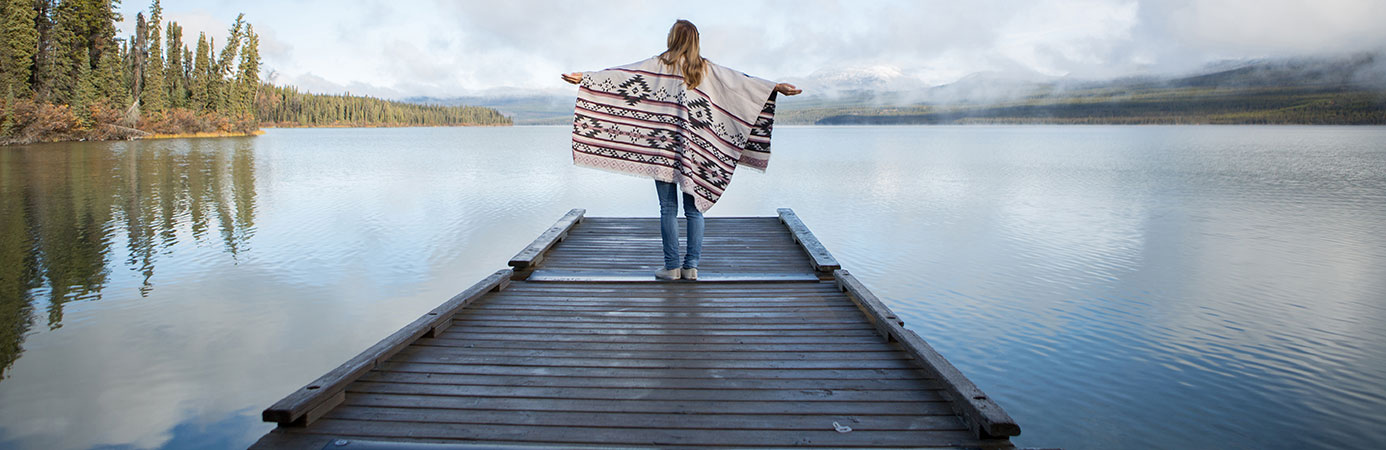 Woman standing on a dock with her arms outstretched