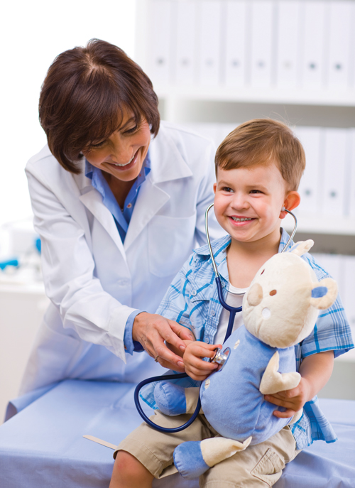 Smiling doctor helps young boy hold stethoscope to his stuffed toy.