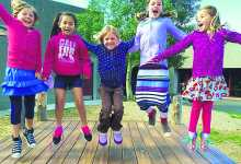 a line of happy girls jumping