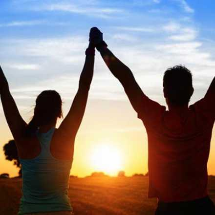 Couple holding hands in the air at sunset