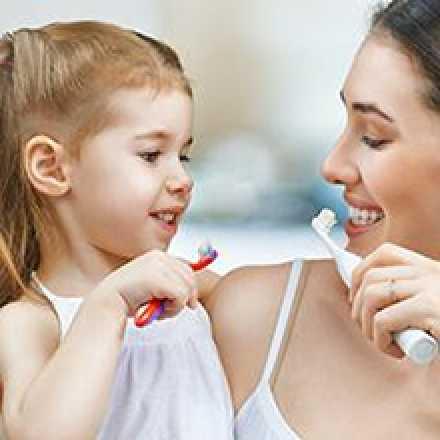 Woman and girl brushing teeth