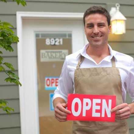 Shop owner holding open sign