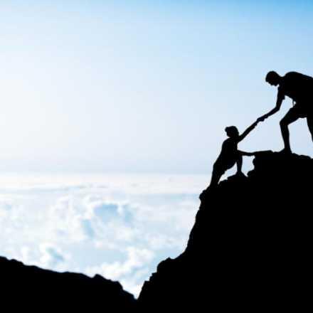 Man helping someone climb up a rock