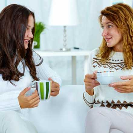 Two women sitting on a couch drinking coffee