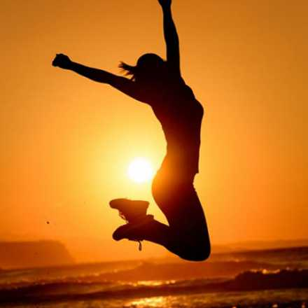 Woman jumping in the air at sunset at the beach