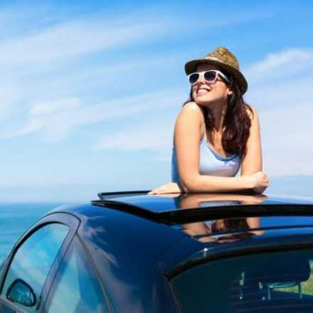 Woman with head out of sunroof at the beach