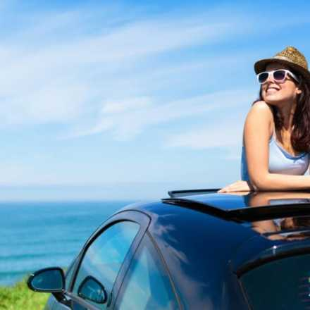 Woman looking out of car sunroof overlooking the ocean