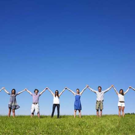 Group of people standing in a field with their arms raised