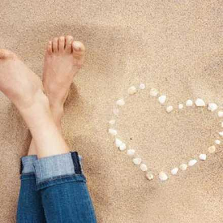 Bare feet in the sand with seashells making a heart shape