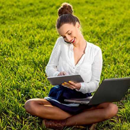 Woman sitting on a lawn with an ipad and laptop
