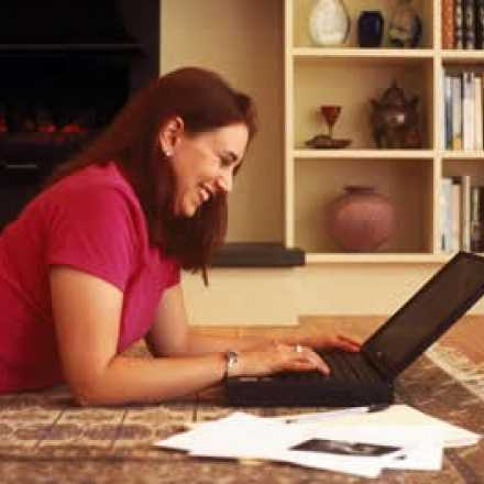 woman lying on the floor looking at her laptop