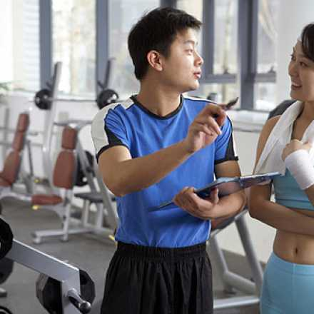 Trainer working with a client at the gym
