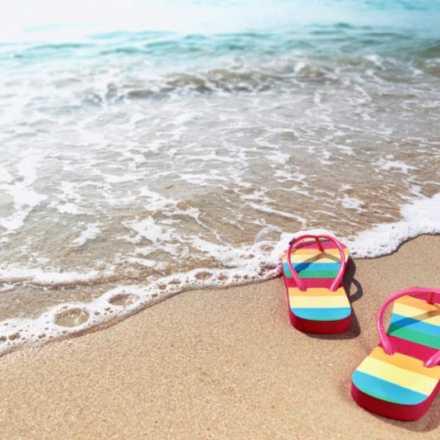 rainbow flip flps on a beach