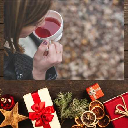 Woman drinking tea with presents in the background