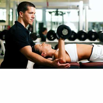 Personal trainer with woman lifting weights