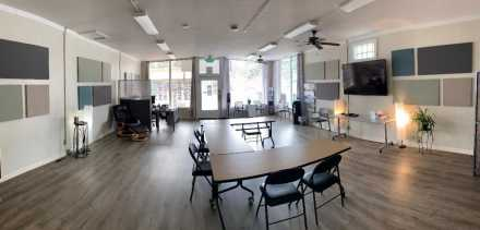 Room at center with bright windows and a table and chairs