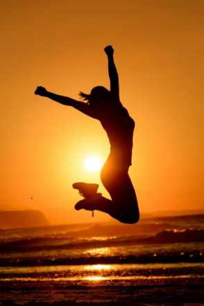 Woman jumping in the sunset at the beach