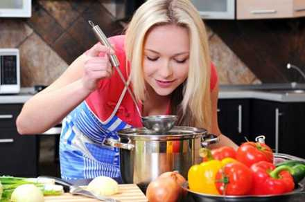 woman tasting soup she is cooking