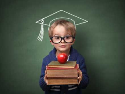 Kid with books and apple in front of chalk board with graduation hat drawn on it.