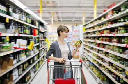 Woman looking at a food label at the grocery store