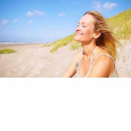 Woman at beach enjoying the breeze