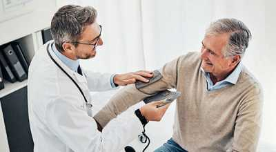 Doctor checking a male patient's blood pressure