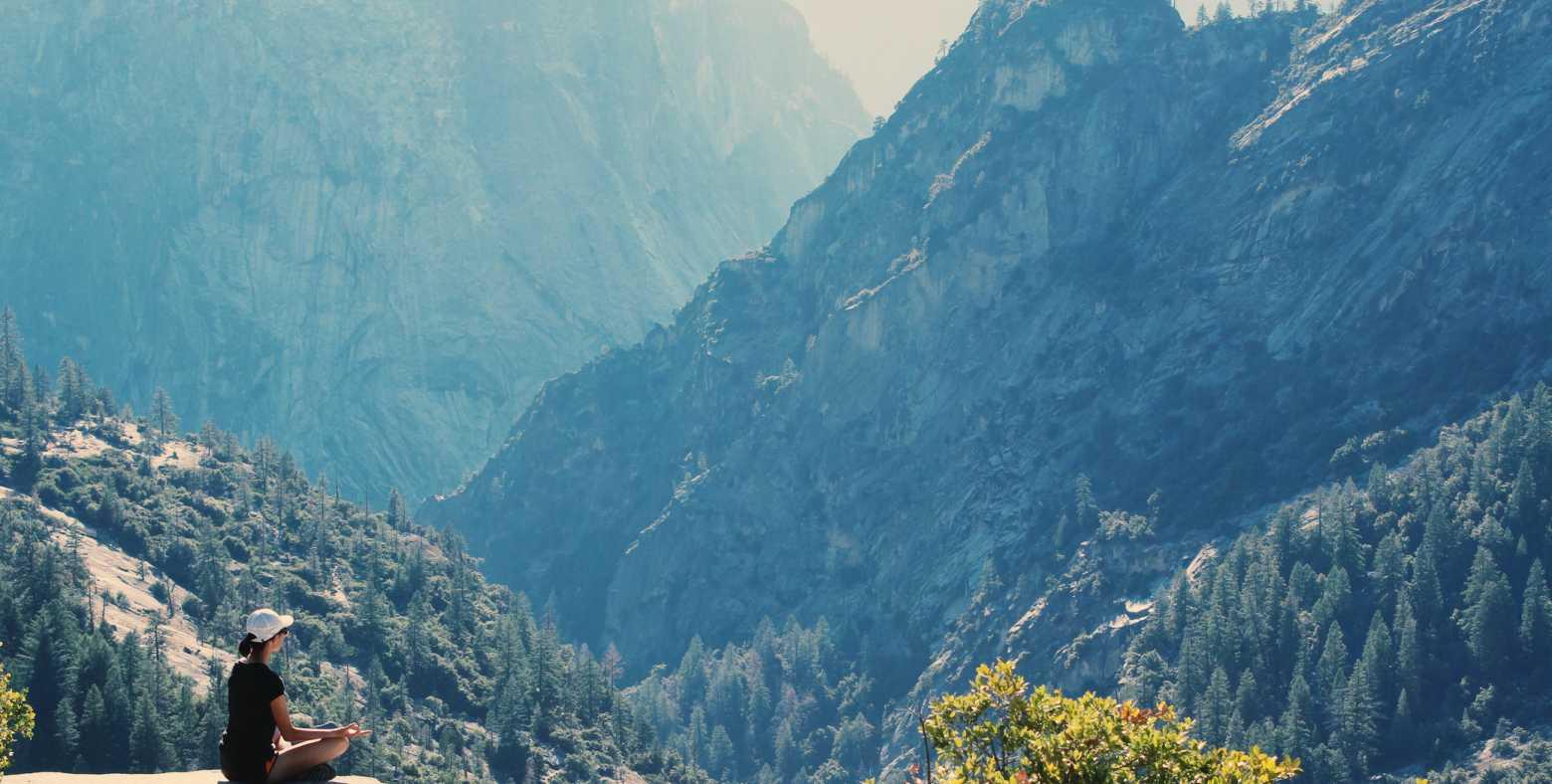 female meditating on cliff on mountain range