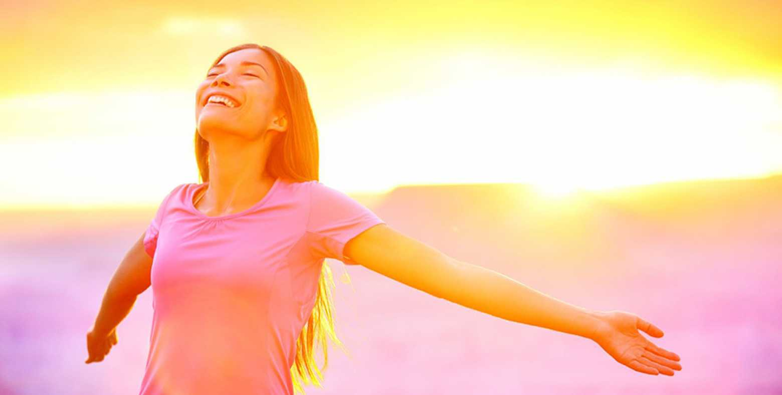 Woman standing with arms stretched out a sunrise