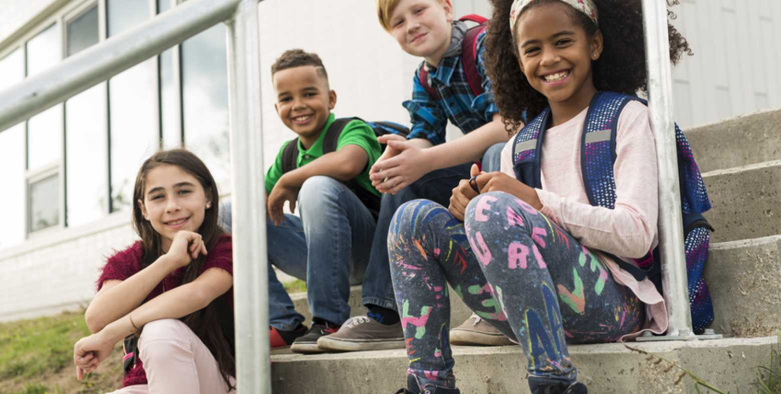 preteens at school sitting on stairs