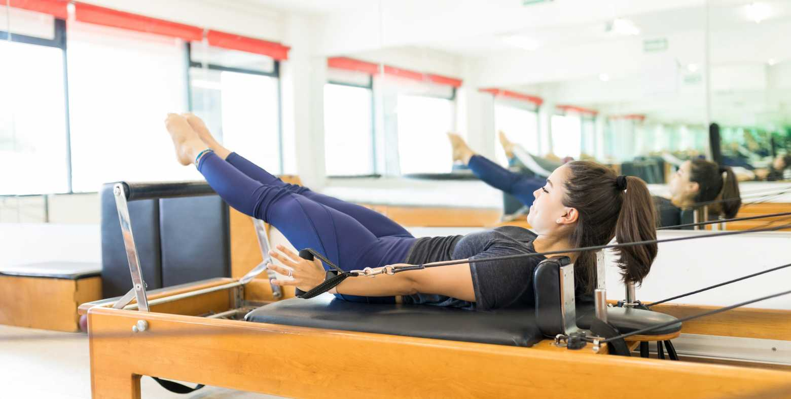women on pilates reformer