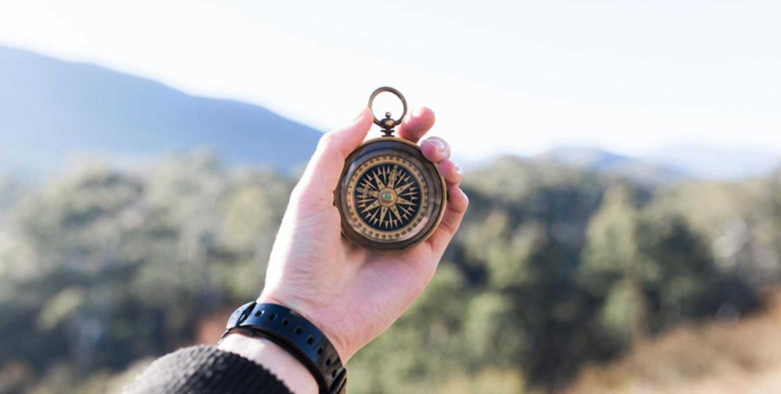 Person holding an old-fashioned compass
