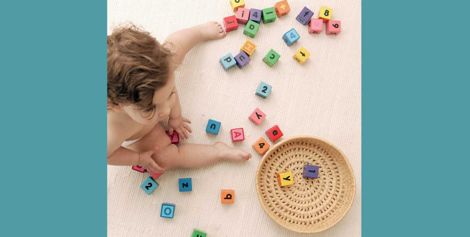 aerial view of toddler playing with toy letter and number blocks
