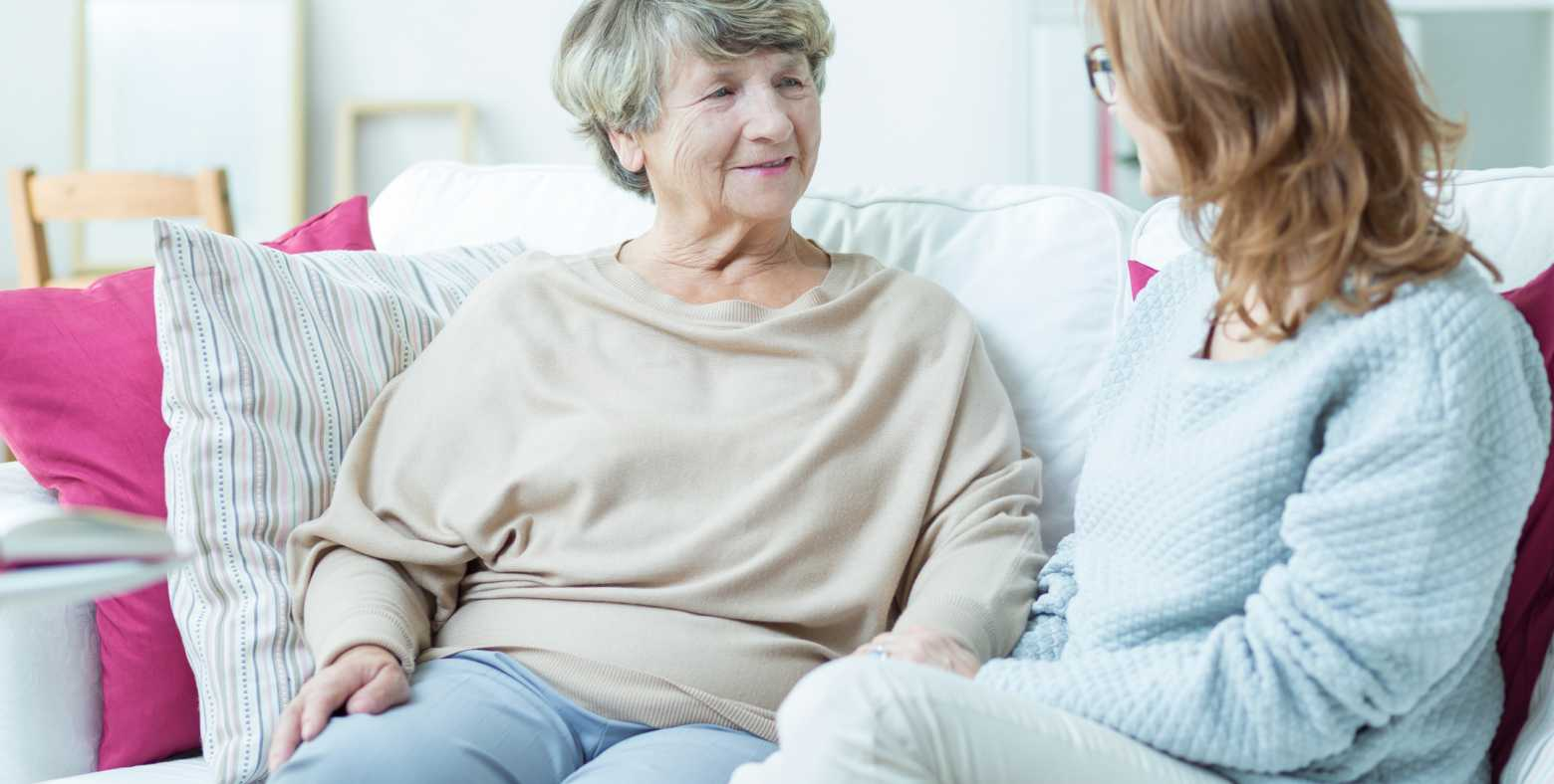 young woman and elderly woman talking on couch