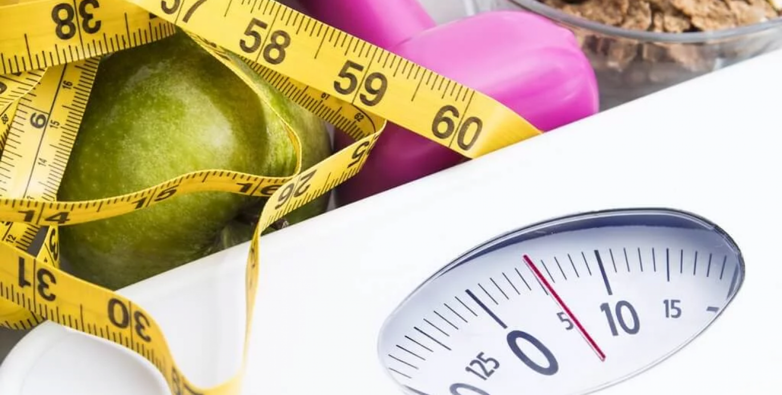 scale, measuring tape, pink dumbbell and green apples