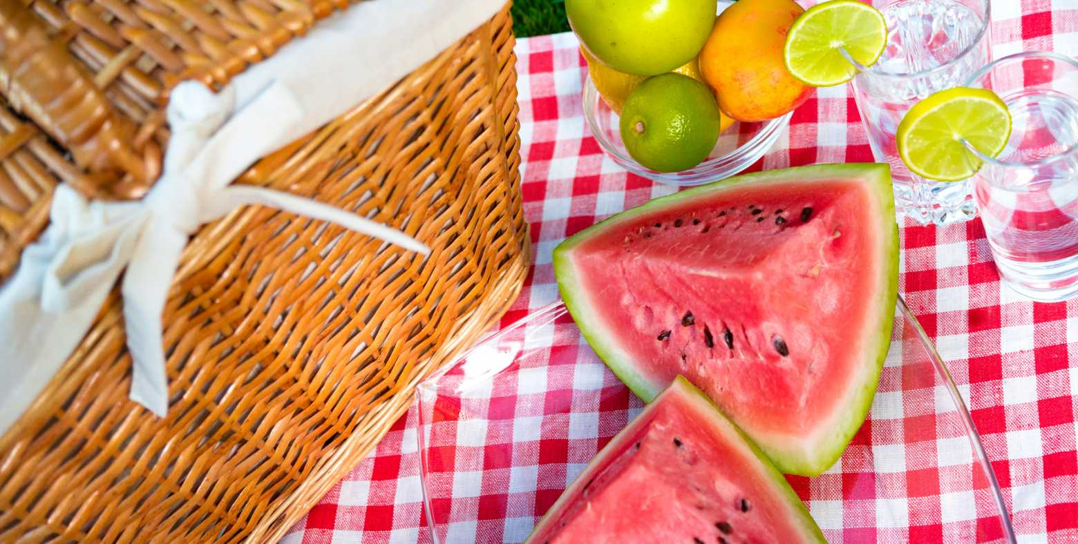 picnic basket and fruits on mat