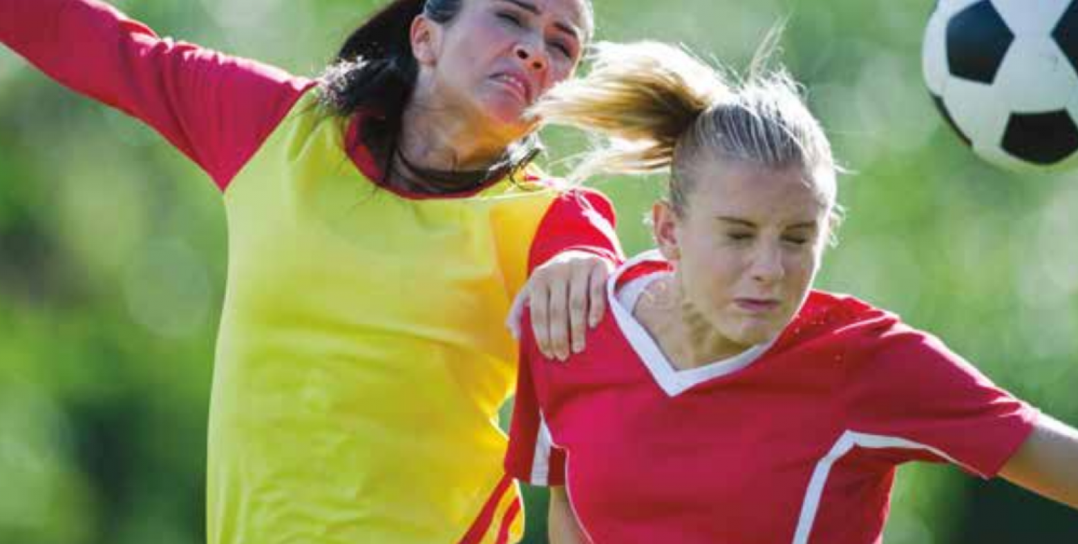 Two women going for a header in a soccer game