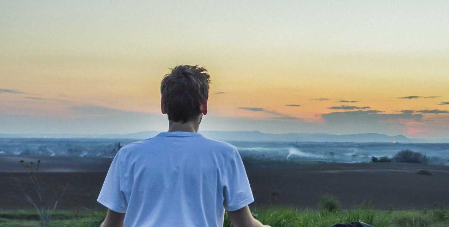 man meditating in front of ocean
