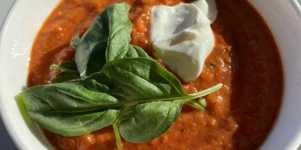 bowl of roasted red pepper and tomoto soup with fresh basil