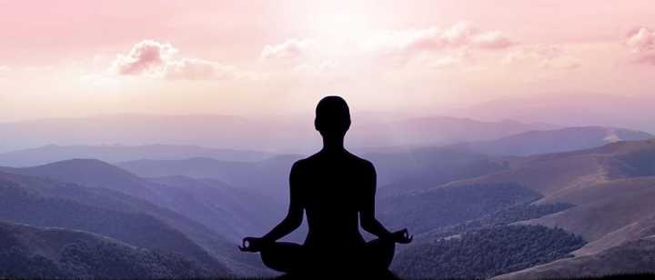 Woman meditating overlooking mountains at sunrise