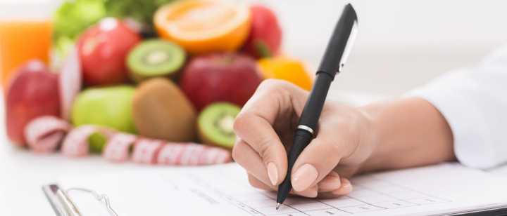 nutrition professional writing notes on clipboard with fruits in background
