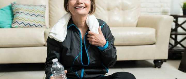 smiling senior woman sitting on yoga mat at home