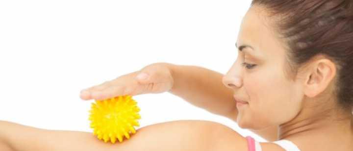 woman rolling massage ball on arm