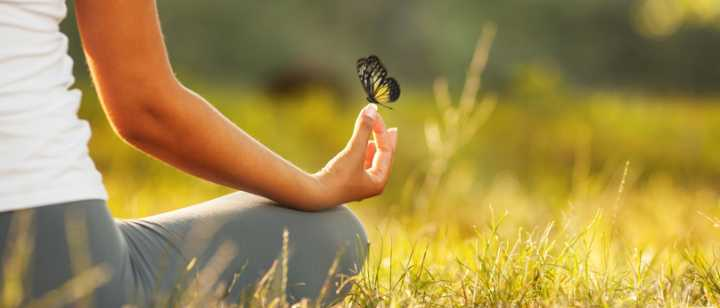 woman meditating in a sunny field